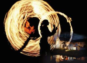 Eine Feuershow und die illuminierte Dorenburg erwarten die Besucher beim Romantischen Weihnachtsmarkt im Niederrheinischen Freilichtmuseum. Foto: OpenMind ManagementService